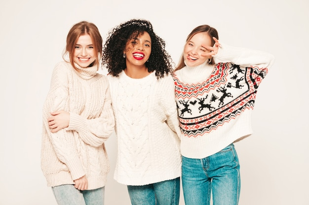 Three young beautiful smiling hipster girls in trendy winter sweaters. positive models having fun and hugging