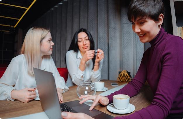 ノートパソコンとテーブルに座って、カフェでプロジェクトに取り組んでいる3人の若いビジネス女性。チームワーク、ビジネス会議。フリーランサーが働いています。