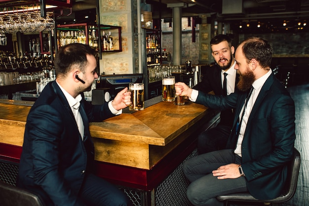 Three young businessman sit at table and hold cips of beer. they talk. people wear suits. first guy has black headphone in ear.
