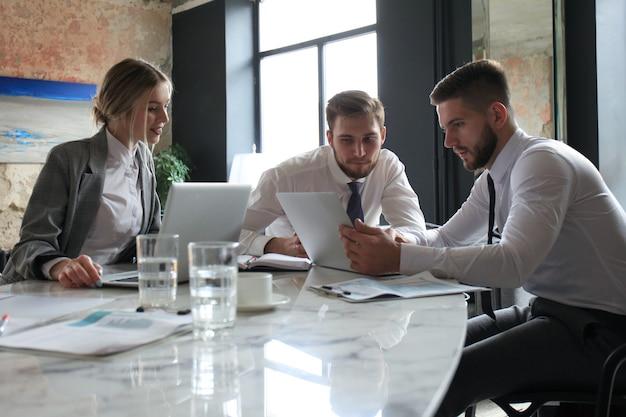 Трое молодых предпринимателей обсуждают бизнес на встрече в офисе.