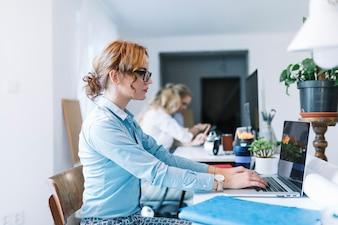 オフィスでお互いに話す職場に座っている3人の若い経済婦
