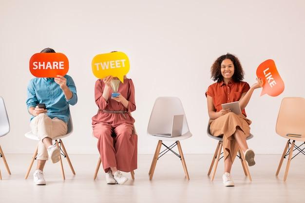 소셜 네트워크에서 의사 소통하는 동안 여러 가지 색의 종이 연설 거품을 들고 모바일 장치를 사용하는 세 명의 젊은 캐주얼 친구