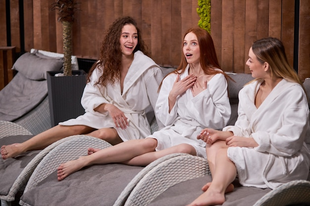 스파와 웰빙 센터에서 함께 휴식을 취하고 대화를 나누고 휴가를 즐기는 세 젊은 백인 여성