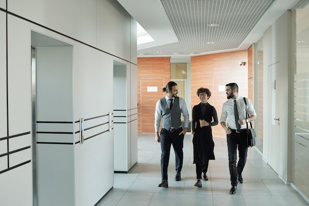 Three young cheerful colleagues in formalwear chatting on their way to office while passing by elevator after coffee break