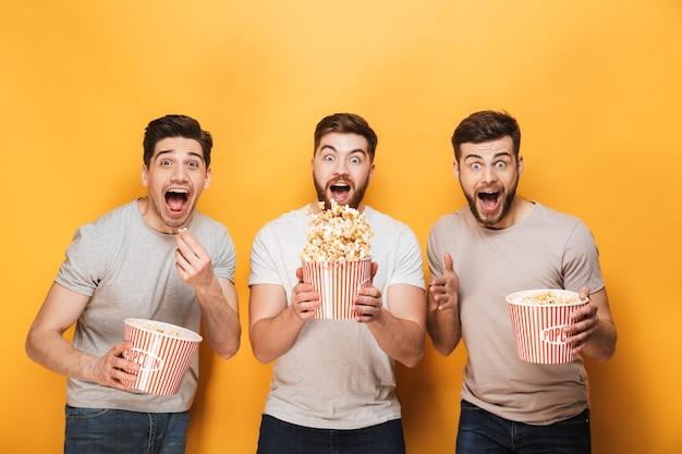 Трое молодых веселых мужчин едят попкорн