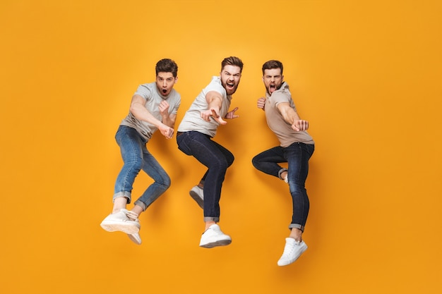 Three young cheerful men jumping together