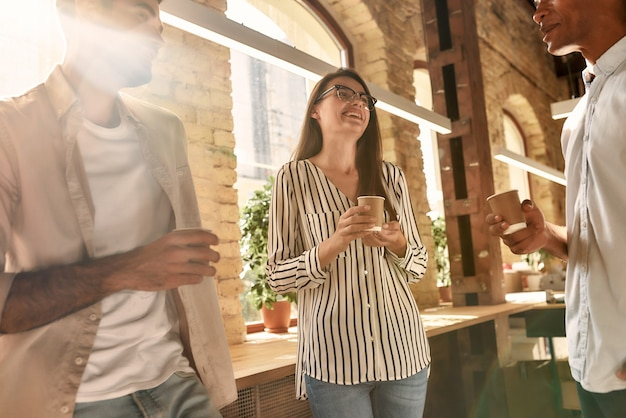 Three young and cheerful people in casual wear holding coffee cups and discussing something