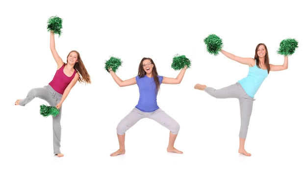 Three young cheerleaders posing over white