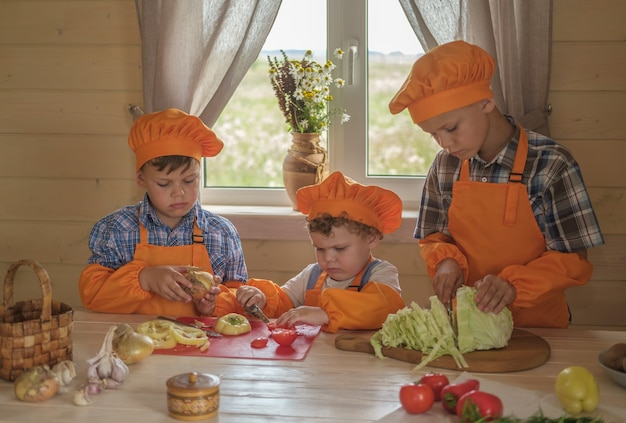 Трое молодых поваров режут овощи для вегетарианского супа на столе в загородном доме.