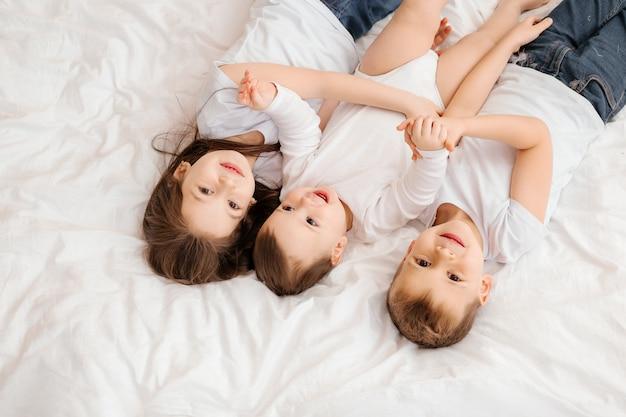 Трое маленьких детей лежат в постели и обнимаются, вид сверху. братья и сестры, большая семья