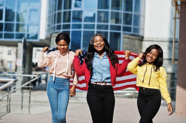 アメリカの国旗を持つ3人の若い大学アフリカ系アメリカ人女性の友人。