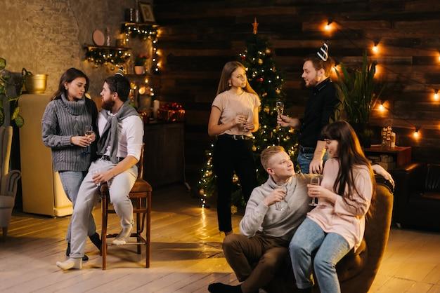 3人の若いカップルが居心地の良い家でクリスマスや新年を話し、祝っています。ガーランドと背景にお祝いのイルミネーションと木製の壁とクリスマスツリー。