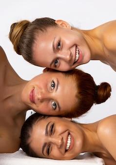 Три молодые, милые девушки позируют, улыбаясь на белой стене. портрет красоты женщины, вертикальный. фото высокого качества