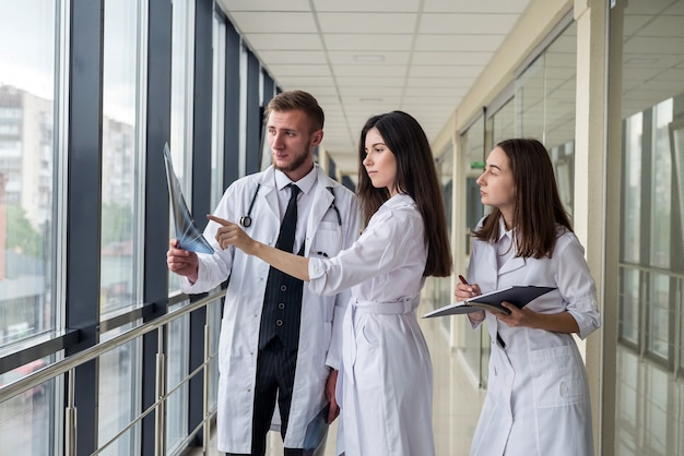 3人の若い医師が、現代の病院の廊下で患者の頭をmriスキャンした結果について話し合っています。健康