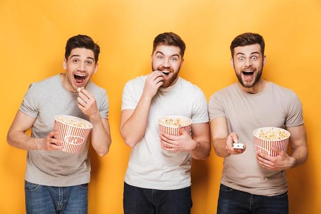 ポップコーンを食べて興奮している3人の若者