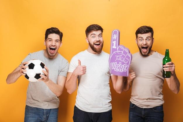 Трое молодых возбужденных футбольных фанатов празднуют