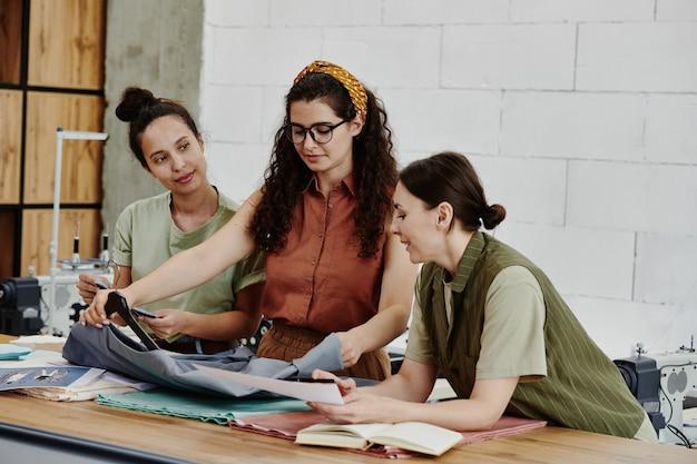 새로운 시즌 콜라보레이션에서 미완성 된 회색 재킷을보고있는 세 명의 젊은 패션 디자이너가 직물의 품질을 논의합니다.