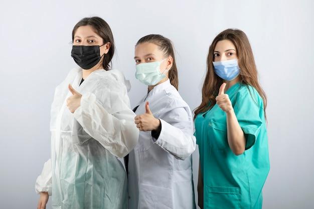Три молодых женщины-доктора стоя и показывают палец вверх