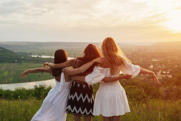 3人の若い女性の友人が抱き締めて、日没の丘で夏のピクニックをしています。