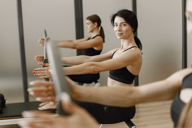 Three young fit women training in gym. women wearing black sportwears. caucasian girls excercising with equipment.