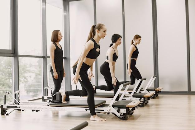 Трое молодых подходящих женщин тренируются в тренажерном зале с женским тренером. женщины в черной спортивной одежде. кавказские девушки занимаются спортом на тренажере.