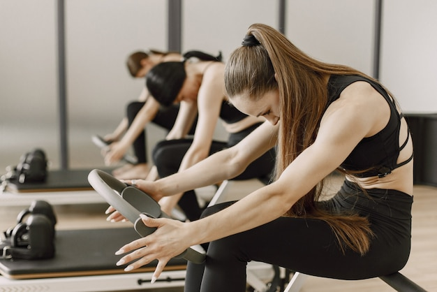 Тренировка трёх молодых подходящих женщин в тренажерном зале. женщины в черной спортивной одежде. кавказские девушки занимаются спортом на тренажере.
