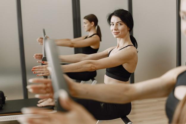 ジムでトレーニングしている3人の若いフィット女性。黒のスポーツウェアを着ている女性。装備を使って運動する白人の女の子。