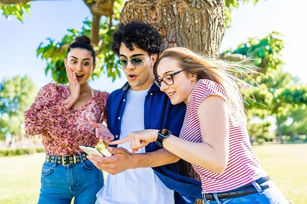 モバイルセルでソーシャルネットワークを楽しんでいるスマートフォンを指している驚きの顔を持つ都市公園の3人の若い友人。 wi-fiインターネット接続技術で自然の中で一緒に楽しんでいる若者