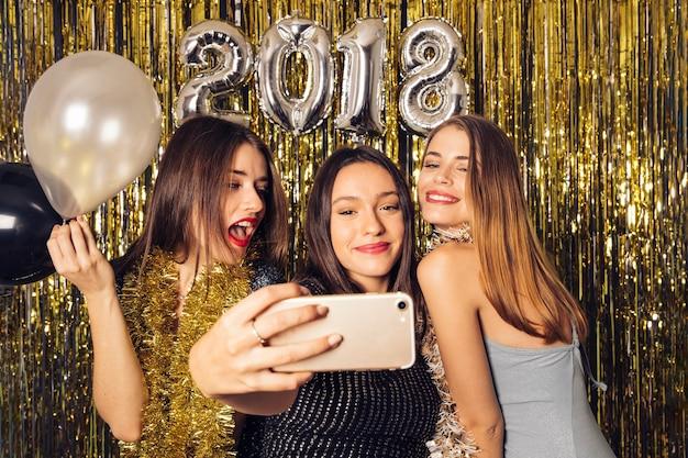 Tre giovani amici che prendono selfie sulla celebrazione del nuovo anno