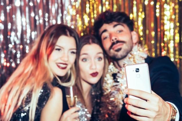 Tre giovani amici che prendono selfie per il partito di nuovi anni