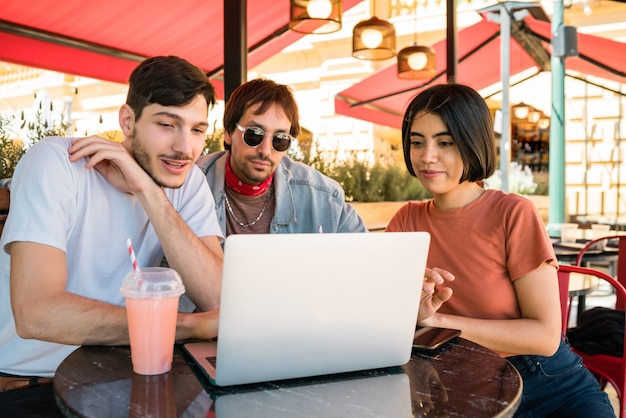 Three young friends using laptop at coffee shop.