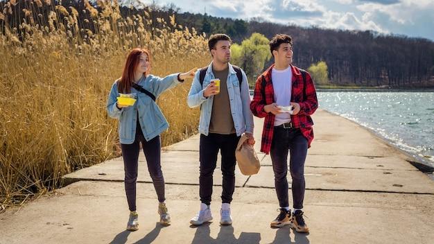 Tre giovani amici passeggiano lungo il lago, bevono e mangiano in un parco