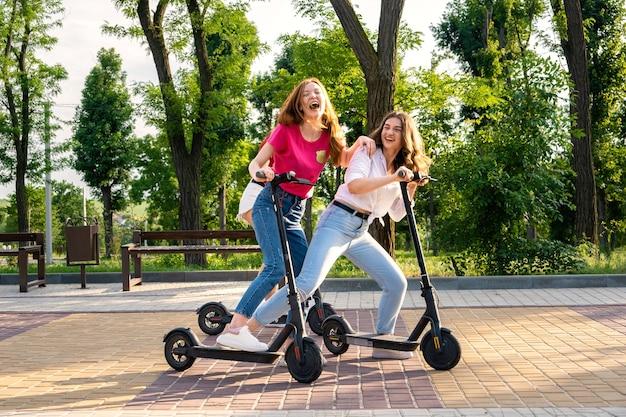 電動スクーターの運転を楽しんで休暇中の3人の若いガールフレンド