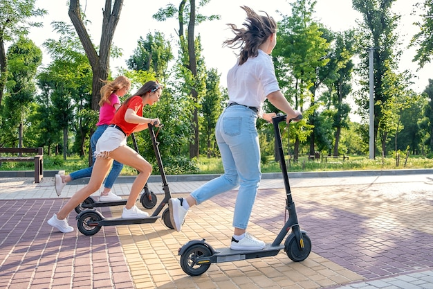 Three young girl friends on vacation having fun driving electric scooter