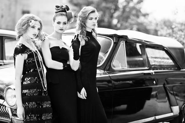 Три молодые девушки в стиле ретро платье возле старых классических старинных автомобилей.