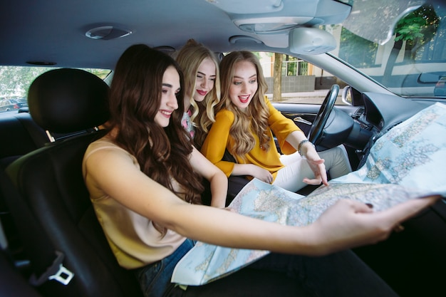 Three young girlfriends traveling in a car.