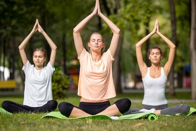 暖かい日に公園の緑の芝生の上のヨガマットに座ってヨガをしている3人の若い女の子。