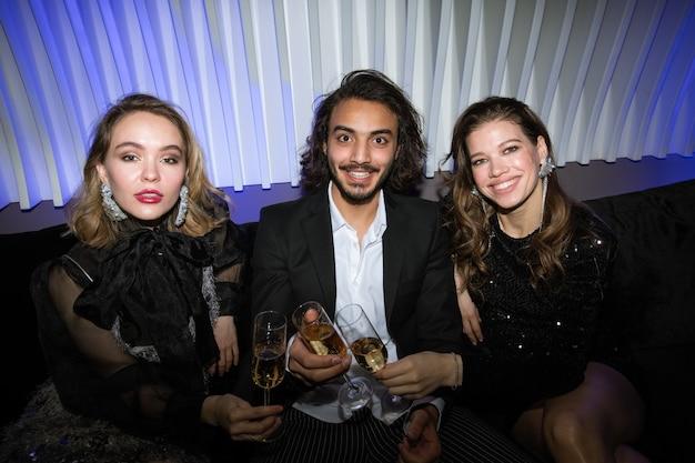 Трое молодых гламурных друзей с бокалами шампанского сидят на диване в ночном клубе, жарят и наслаждаются вечеринкой