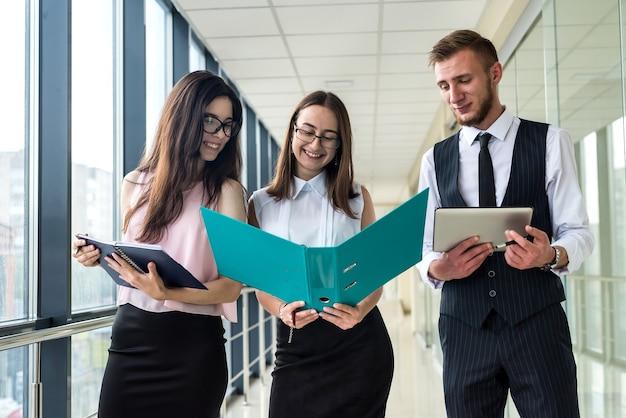사무실 복도에 서 있는 동안 세 명의 젊은 행복한 비즈니스 파트너가 계약 또는 보고서에 대해 논의합니다.