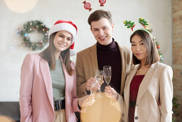 クリスマスの乾杯中にシャンパンでチャリンという音を立ててあなたを見ている3人の若い幸せな異文化ホワイトカラー労働者