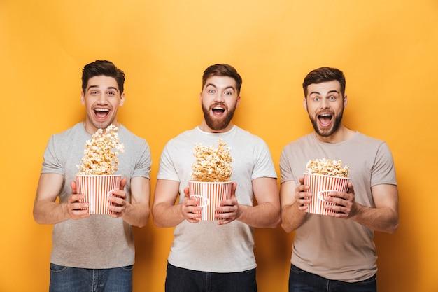 ポップコーンを食べて3人の若い幸せな男性