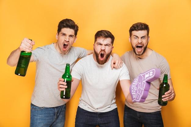 Трое молодых счастливых мужчин держат пиво и празднуют