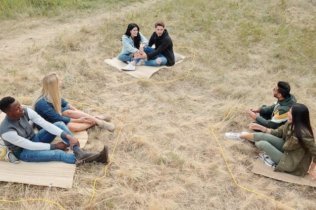서로의 앞에 마른 잔디에 앉아 야외에서 휴식을 취하는 동안 사회적 거리를 유지하는 세 젊은 이문화 커플