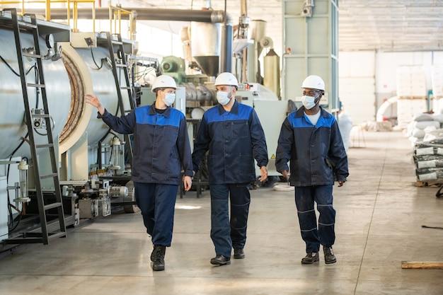 산업 공장을 따라 이동하고 새로운 처리 장비에 대해 논의하는 대형 현대 공장의 세 젊은 이문화 노동자