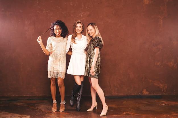 Три молодых международных красивых брюнетки в модном летнем блестящем платье.