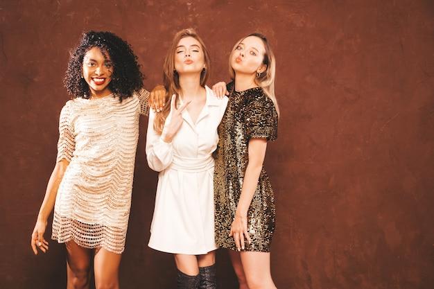 Tre giovani belle donne castane internazionali in abito lucido estivo alla moda.