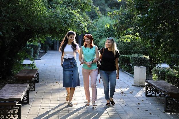 세 젊은 즐거운 여자 친구가 공원에서 천천히 걷고있다