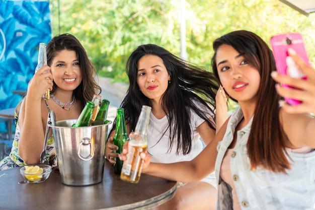 セルフィーを撮り、ビールを飲む3人の若いラテン系の友人写真を撮るガールフレンド