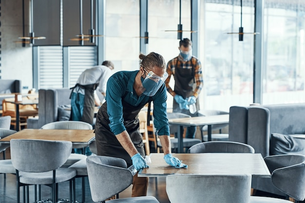 Трое молодых официантов мужского пола в столах для чистки защитной спецодежды для клиентов в ресторане