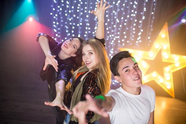 세 명의 젊은 남성과 두 명의 여성이 파티의 나이트클럽에서 즐거운 시간을 보낸다